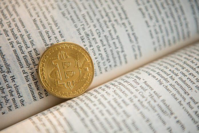 Bitcoin-Begriffe: Eine Bitcoin-Münze liegt in einem Buch